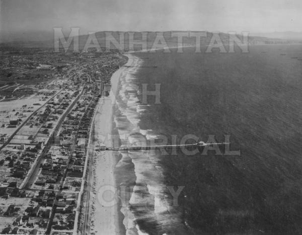 Aerial photo from about 17th Street looking south with undeveloped Palos Verdes in the distance.  The Manhattan Beach pier was completed in 1920 and was a state historic landmark in 1995 as it is the oldest concrete pier on the West Coast.  Note the wooden fishing extension that was built in 1928 and was destroyed by a winter storm in 1940/41.