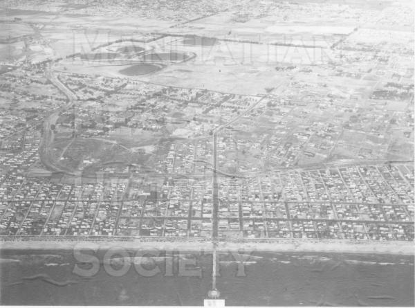Aerial view of Manhattan Beach.  There was a large building boom arter the war but there are still many vacant lots shown.  Note the dark ovals of the Chevron tank farm which is now the Manhattan Mall, Marriott hotel, and Manhattan Village.