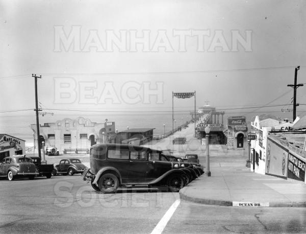 The Manhattan Beach Pier, as seen looking down Center St. (now Manhattan Beach Blvd.).  The neon sign was built by Metlox Industries in the late 1920s. The two buildings at the foot of the Pier served as a waiting room for the Pacific Electric Red Car (south building) and a restaurant (north building).  The Red Cars along the South Bay beaches were discontinued because of poor ridership in 1940.