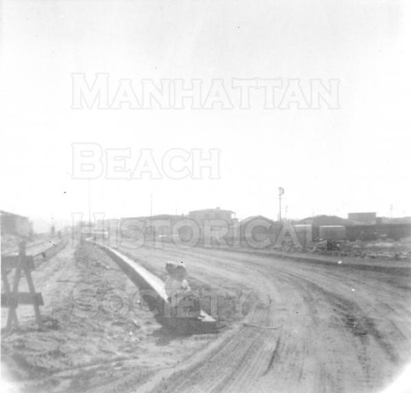 This photo is looking south down Valley Dr. from Manhattan Beach Blvd.  From 1920 to 1966, Valley Dr. (formerly West Railroad Dr.) did not extend from 15th St. to 10th St.  This was because Metlox Potteries owned the property and used it for warehouse space and a railroad spur.  After Metlox deposed of the spur and warehouse and sold the property to Manhattan Beach, the City extended and paved Valley Dr. in 1967.