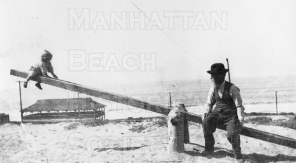 Pecks Pavilion in Background, on the beach between 26th and 27th St..  James E. Bott and his granddaughter.
