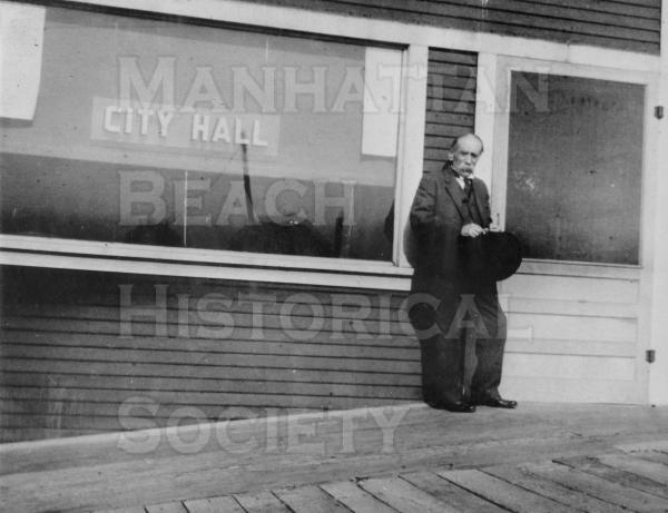 A.C. Conner, the first City treasurer and landscape artist, standing in front of the first city hall.  This was the converted real estate office of John A. Merrill and was located at 125 Center St. now Manhattan Beach Blvd.