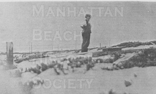 F.S. Daugherty on the sand dunes with ocean in the background.