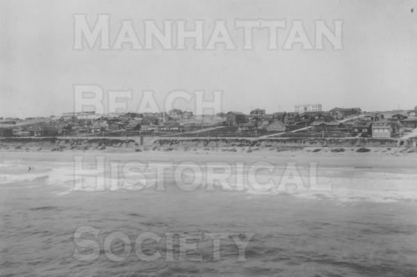 The Strand with Manhattan Beach in the background, looking northeast from the New Pier. On the extreme right is the first Neptunian Club which stood at 12th St. and The Strand.  The new city hall at 15th Street and Highland Avenue is above that and to the left.