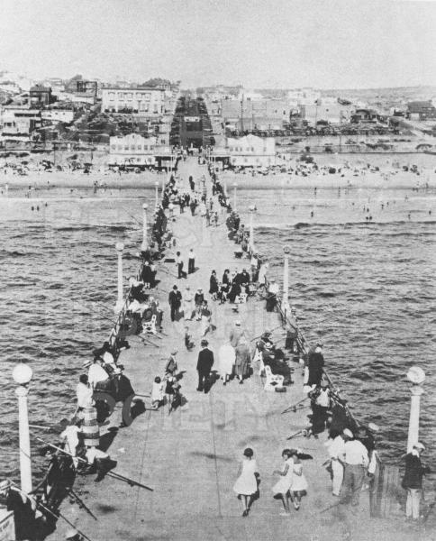 View from the roof of the Manhattan Beach Pier roundhouse on Memorial Day, 1930.  Pier strollers are formally dressed, except the young lady in the swim suit on the left of the photo who was disobeying the City rules.