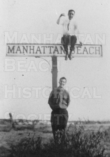 Manhattan Beach sign at Center St. (M.B. Blvd.) and East Railroad Dr. (Ardmore Ave.) by Santa Fe Rairoad Co.  This sign was adjacent to a small depot for the Santa Fe Railroad.