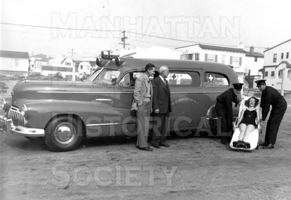 Mayor Charles Blech and Councilman Claude Clemens with two fire fighters and a simulated accident victim in front of a 1948 Buick ambulance.  There were two firemen in each shift with first aid training that would drive and attend the ambulence.