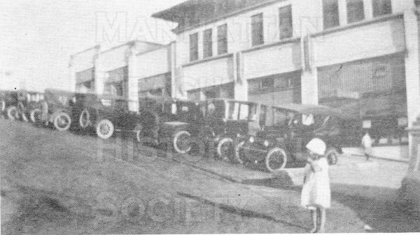 "The young Miss. Withers next to parked cars at the foot of Marine Ave.  The Sadler Bldg. and the adjacent Marine Pavilion (not shown) served as the ""second downtown"" area for the residents of north Manhattan Beach."