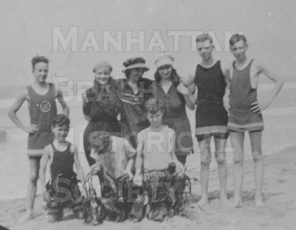 Men and women on the beach in bathing attire for the day.  Note that the boys are holding kelp.