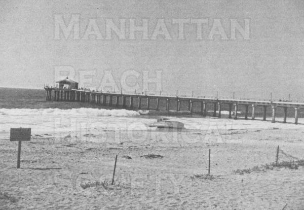 Captain Larson's bait boat and water taxi (between the Pier and the fishing barge) is on the beach.  Note the wooden fishing extension to the Pier has been washed away by the 1940/41 winter storm.  The signs and fence were to keep people off the beach.