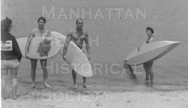 Dale Velzy, Bob Hogan and ? coming ashore at Lake Los Angeles (now part of Marina Del Rey).  They are greated by Dale's wife (wearing a sweat shirt with Velzy and Jacobs surf boards on the back).  Publicity shot for the Catalina Is. to Manhattan Beach Paddleboard Race.