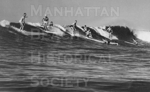 Many surfers.  The surfer with the white cap is Jim Bailey.  From Life Magazine.