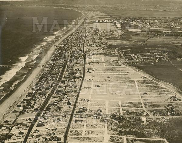 Aerial photo of the Manhattan Beach from above   Looking north from just south of First St., showing the Manhattan Beach Pier, Marine Pavilion, the Standard Oil Pier, and the Hyperion Pier.
