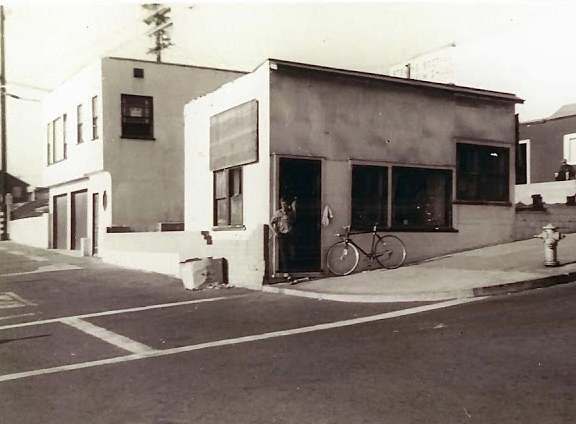 "Dale Velzy in front his ""Velzy Surfboards"" shop, which opened in 1949 and was located at 117 Manhattan Beach Blvd.  This is believed to be the first American surf shop where one could have a custom surf board shaped to one's weight and surfing style. ."