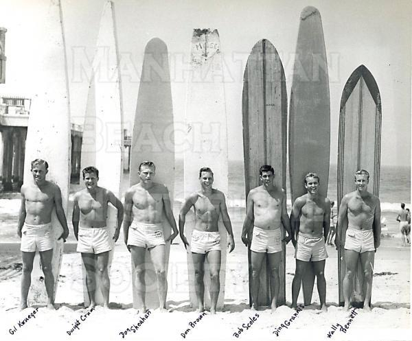 Lifeguards and surfers in front of the Manhattan Beach Pier.