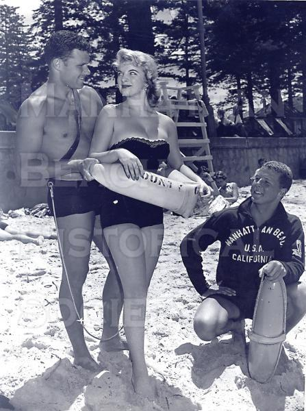 Publicity shot for the International Surf Lifesaving Carnival in Melborne, Australia.  From L-R: an Australian model, Tad Devine (son of U.S. movie actor Andy Devine) and L.A. County lifeguard Dave Balinger (wearing the Manhattan Beach sweatshirt).  They are demonstrating how to wrap the rescue tube (invented by a famous surfer of the �40s, Pete Peterson).